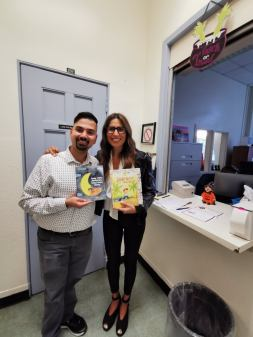 Principal Susanna Ranali and teacher Daniel Rasqunha receiving the books donated by UPAAE